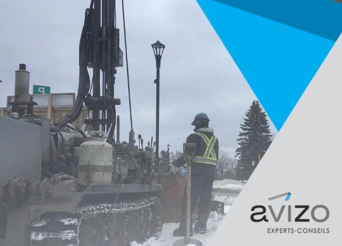 Un ouvrier se tient près d'une foreuse pour effectuer une analyse environnementale de site - Avizo Experts-Conseils