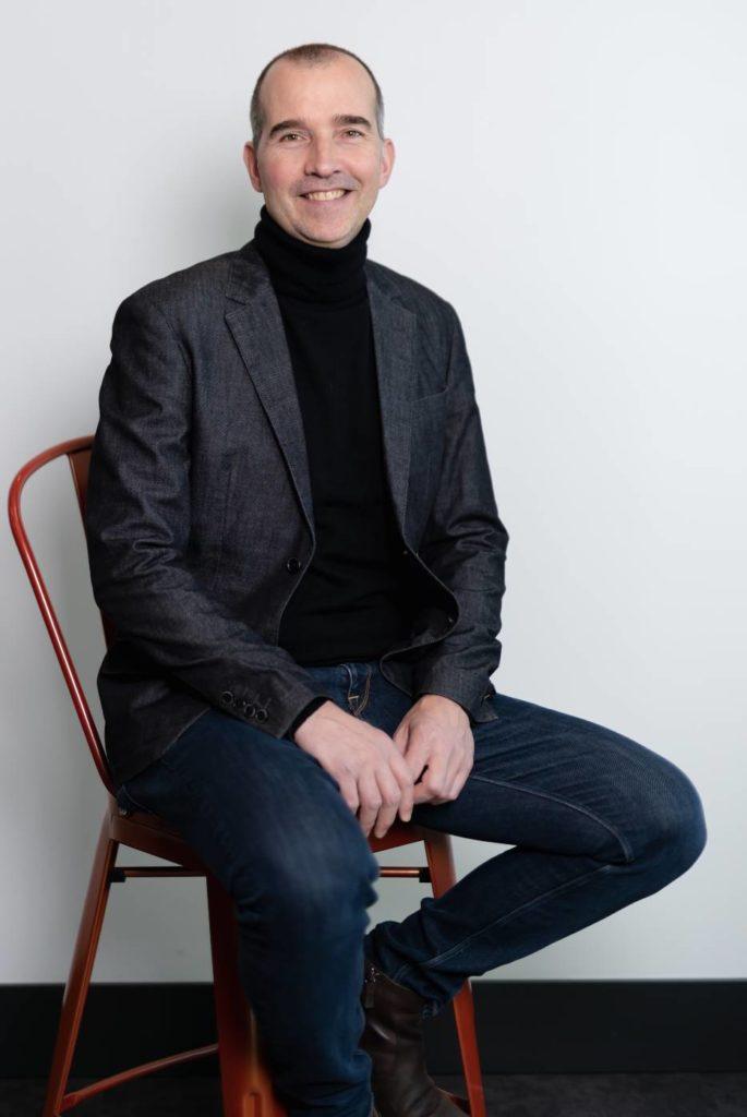 Un homme souriant assis sur une chaise droite