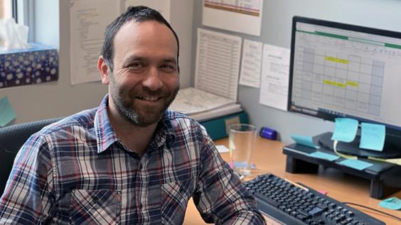 Un homme souriant assis à son bureau