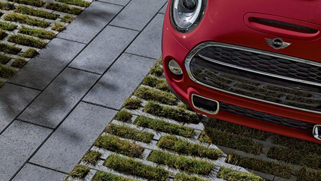 un pavé de béton alvéolé supporte une voiture qui y est stationnée