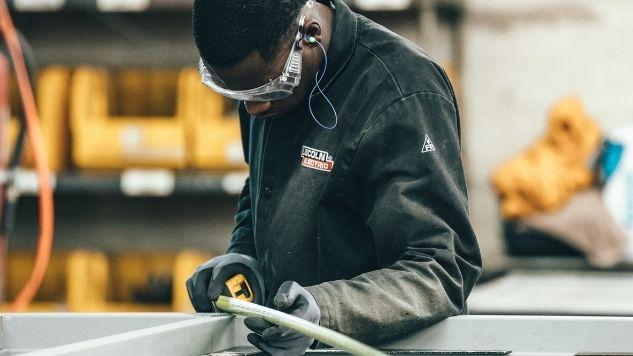 Un employé mesure un cadre formé d'extrusion d'aluminium